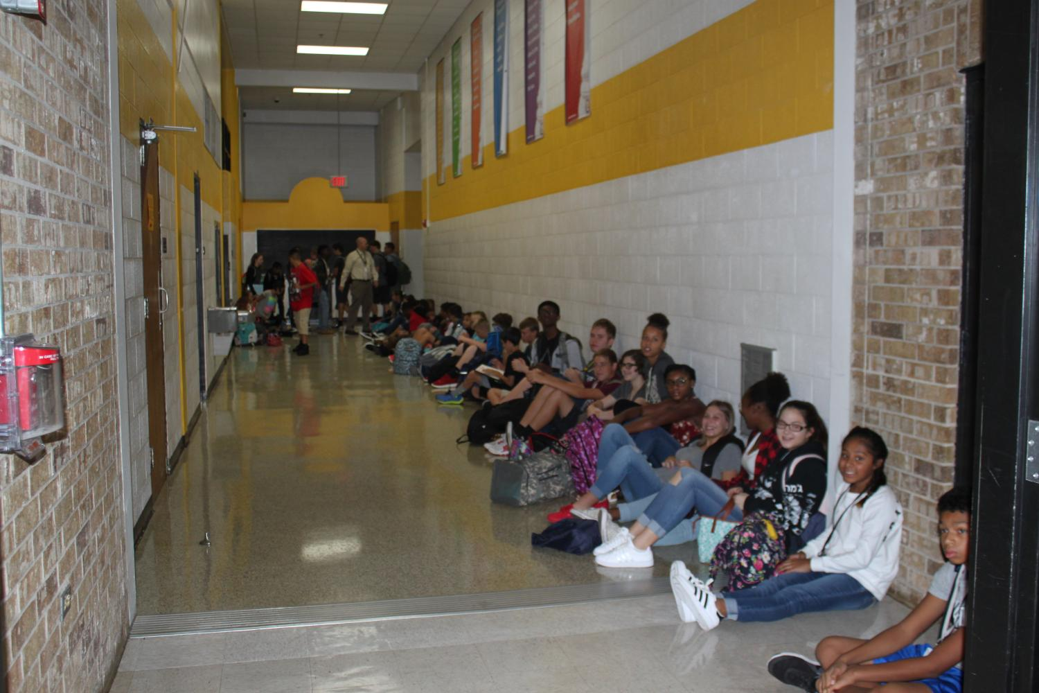 Students sit in overflow area before school.
