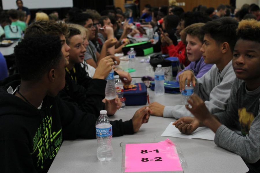 Students eat lunch at team tables