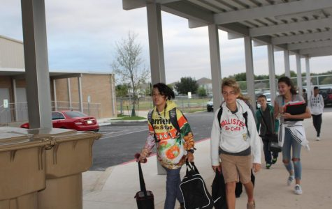 Students walk into Dobie on a cool morning.