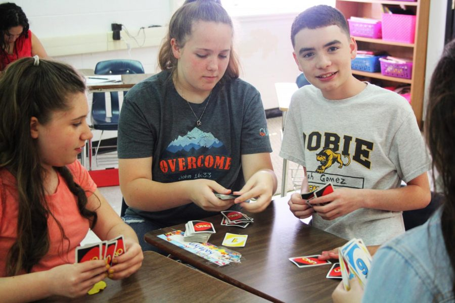 Elijah Gomez,Amber Stossel, and Natasha Ledum playing a game of UNO during cougar time.
