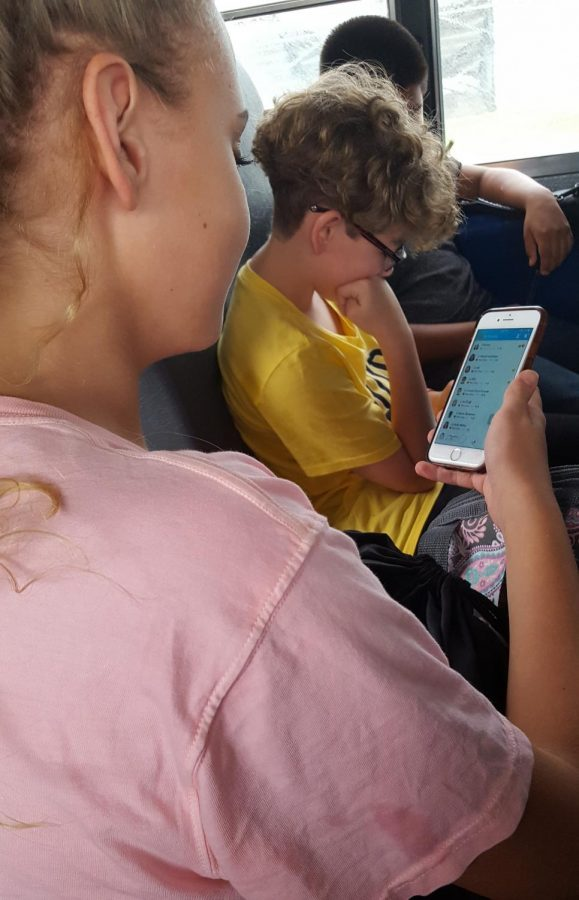 A student uses her phone on the bus.