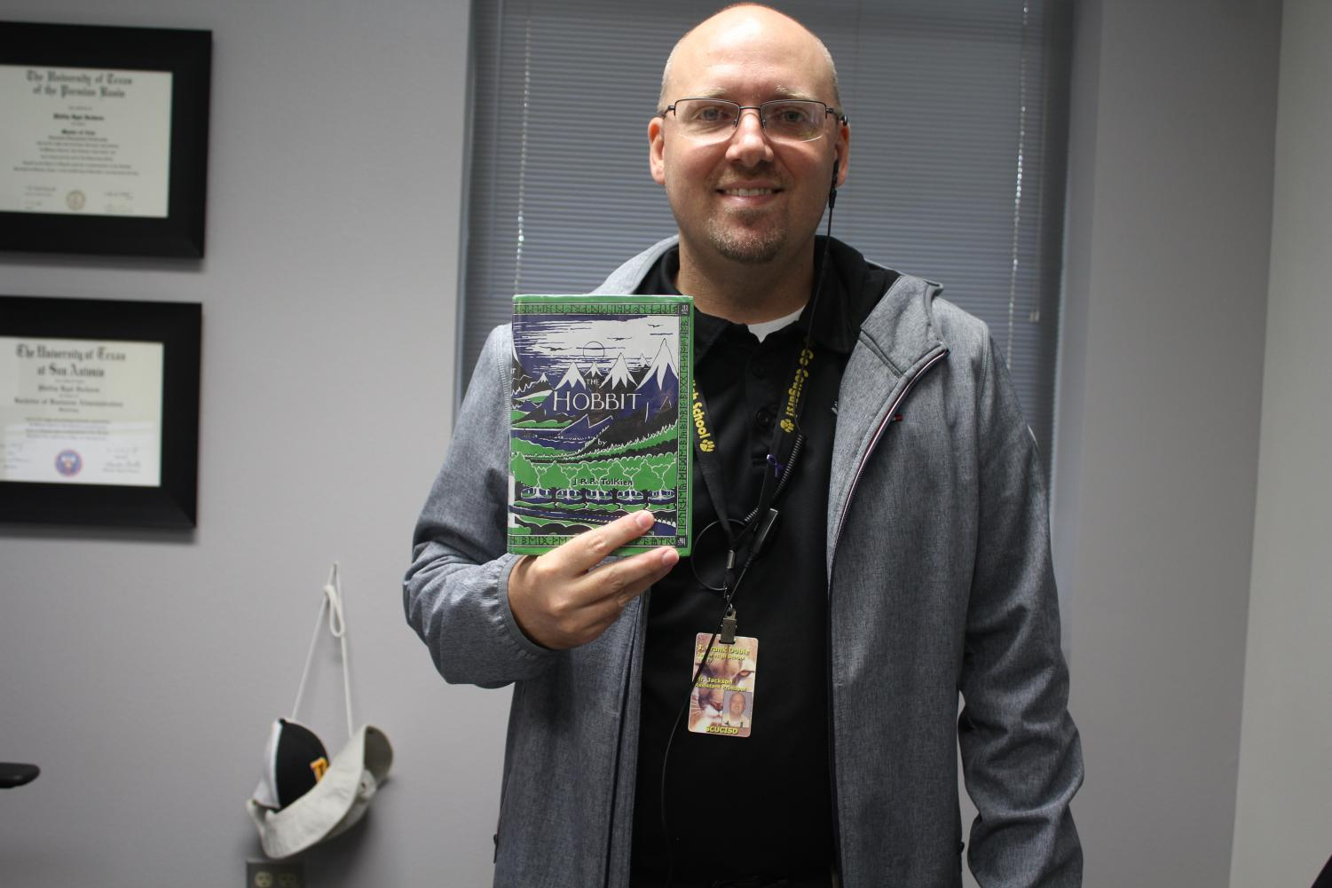 """Mr. Jackson with his book The Hobbit.    Mr. Jackson, a Dobie administrator, said, """"It gives you a better understanding of the world around you."""" He agrees that reading also develops the reader's vocabulary."""