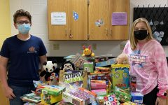 NJHS Treasurer Kyle Banks and President Madison Gastol, 8, pose next to the haul of toys, books, and games for the donations for The Women & Children's Shelter.