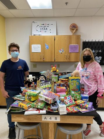 NJHS Treasurer Kyle Banks and President Madison Gastol, 8, pose next to the haul of toys, books, and games for the donations for The Women & Children